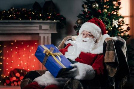 Photo for Santa claus in traditional red costume holding gift box while sitting in armchair - Royalty Free Image