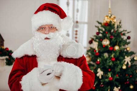 Photo for Santa claus in traditional red costume using smartphone - Royalty Free Image
