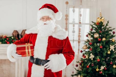 Photo for Santa claus in traditional red costume holding gift box - Royalty Free Image