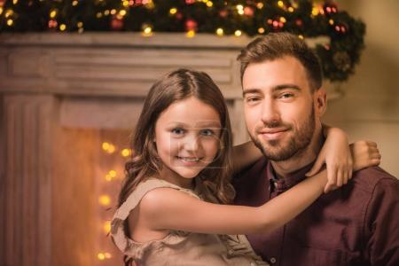 Photo pour Mise au point sélective de père et fille, regardant la caméra tout en restant assis près de cheminée le soir de Noël - image libre de droit