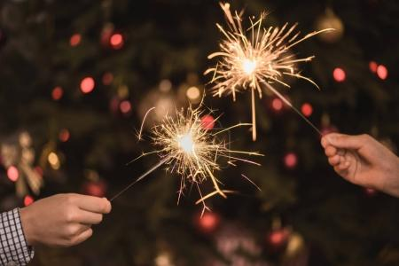 Photo for Cropped shot of kids holding sparklers in hands on christmas eve - Royalty Free Image