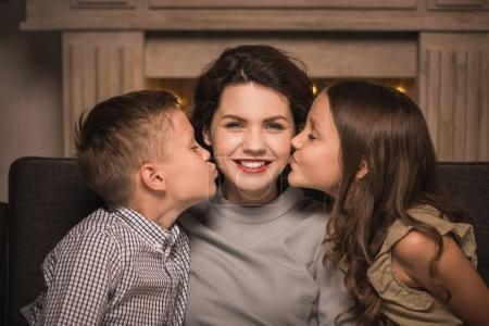 kids kissing smiling mother
