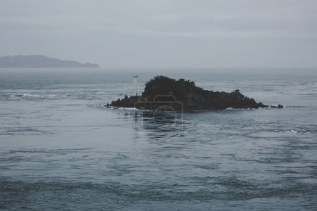 Rock with a lighthouse in the sea, whirlpools Naruto