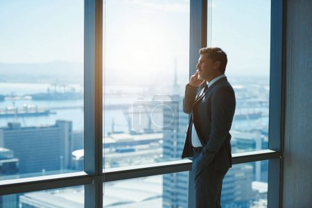 Photo pour Handsome mature business executive standing at large windows in a top floor office, talking on his mobile phone while looking out the view of a city below - image libre de droit