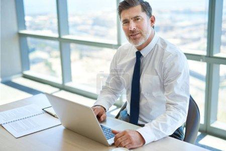 Foto de Retrato de un apuesto ejecutivo maduro sentado en el escritorio de su oficina con su portátil abierto y mirando a la cámara con una expresión positiva. - Imagen libre de derechos