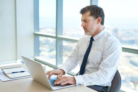 Photo pour Serious mature business executive sitting at his desk in a modern office with large windows, typing on his laptop - image libre de droit