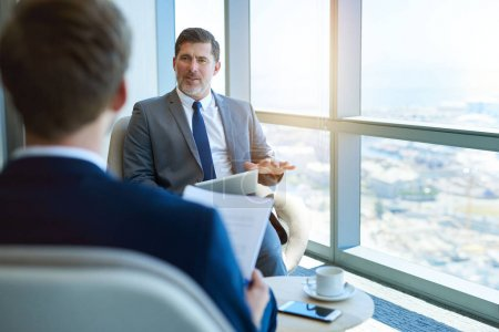 Photo for Handome mature corporate manager sitting in a modern office space, holding a digital tablet while interviewing a young business applicant - Royalty Free Image