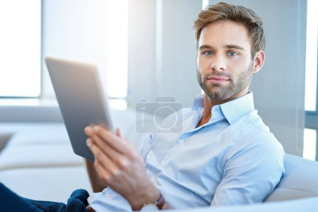Photo for Portrait of a handsome young businessman holding a digital tablet while sitting on a couch and looking at the camera with a positive expression - Royalty Free Image