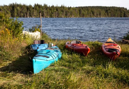 four kayaks in front of a lake