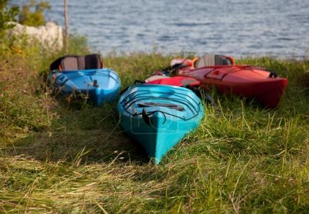 close up of three kayaks by lake