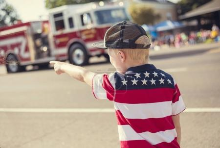 Photo for A rear view of a boy watching a firetruck drive by during a parade procession during an Independence Day parade in a small town in the USA. - Royalty Free Image