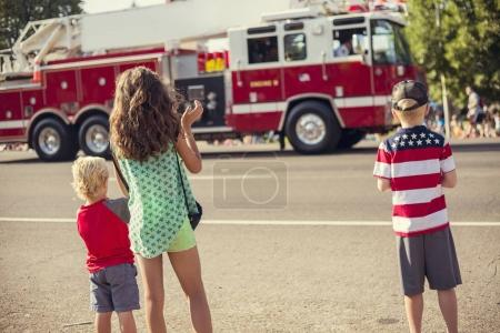 Photo for A rear view of kids watching a firetruck drive by during a parade procession during an Independence Day parade in a small town in the USA. - Royalty Free Image