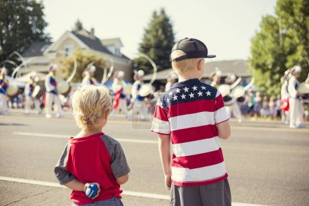Photo for A rear view of kids watching a marching band walk by during a parade procession during an Independence Day parade in a small town in the USA. - Royalty Free Image