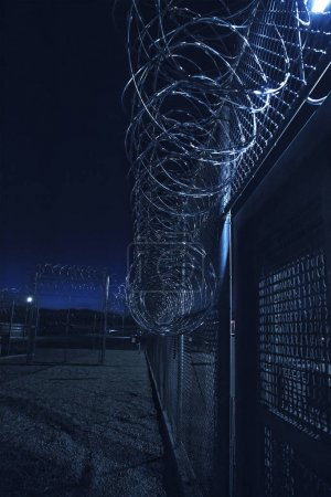 Prison Fence at night. Exterior barbed wire fence that the correctional facility