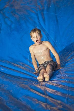 boy sliding down a slip and slide