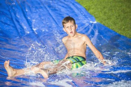 Teen boy sliding down a slip and slide outdoors