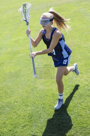 Girls Lacrosse Player running during a Lacrosse game