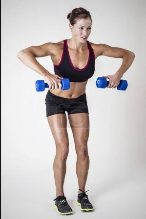 Strong Beautiful fitness woman lifting dumbbell weights
