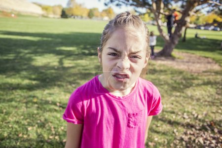 Photo for A little girl having an emotional outburst at the schoolyard. She is angry and upset and showing strong emotions - Royalty Free Image