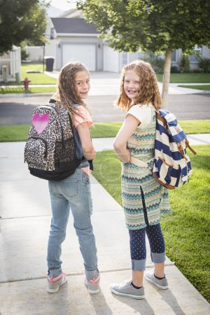 girls with backpacks on going off to school