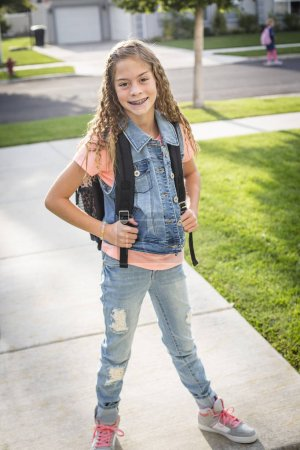 Photo for A cute school girl wearing a backpack heading off to school in the morning. Ready to walk to class - Royalty Free Image