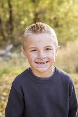 Cute, smiling, young boy portrait outdoors. He's got a big toothless smile