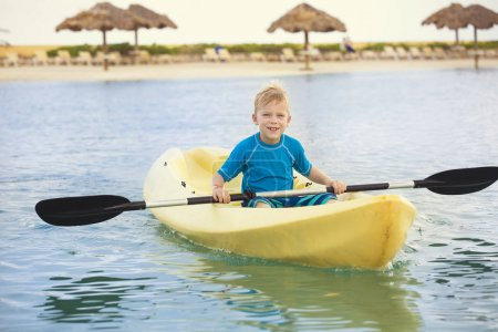 Little boy paddling kayak