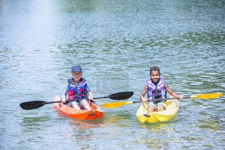 Two boys drifting on kayaks at lake