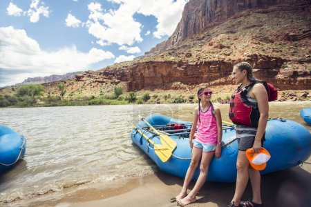 Smiling mother and daughter standing near boats in life jackets against mountains