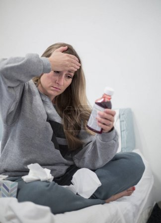 Woman with a head cold looking at the label of a pill or medication bottle