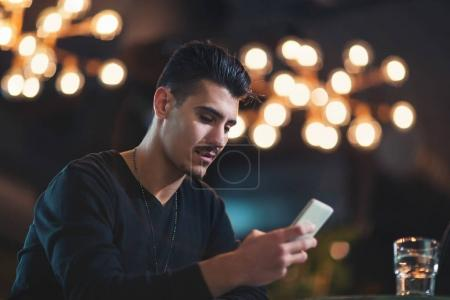 Young man texting with his mobile phone at the bar