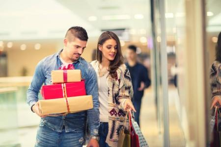 Couple with Christmas presents, gifts and shopping bags in a mall
