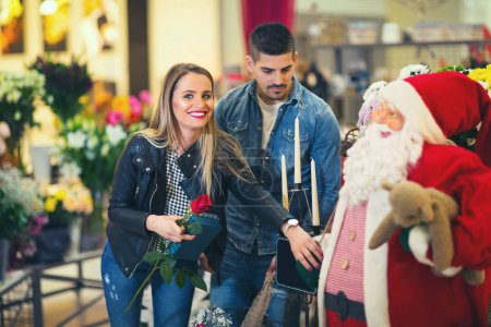 Relations, love, romance concept -  happy young couple with flowers in shopping mall