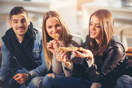 Young people in casual clothes eating pizza, talking, laughing a