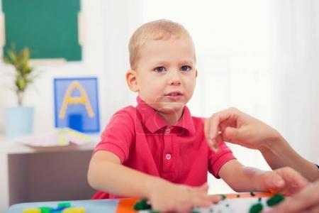 Photo pour Mignon petit garçon moules de pâte à modeler sur table - image libre de droit