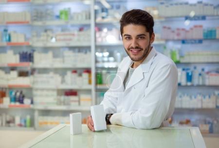 Friendly male pharmacist dispensing medicine holding a box of ta