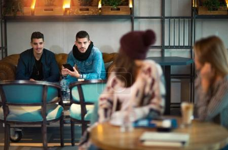 Girls are sitting at a table and waving guys at another table