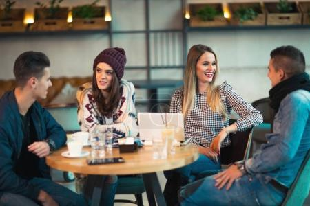 Group of young people sitting in a coffee shop having fun