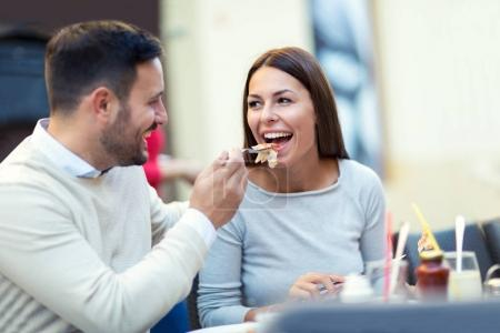 Man feeding his girlfriend with pizza