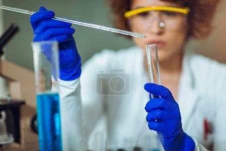Young female scientist in protective glasses and gloves dropping
