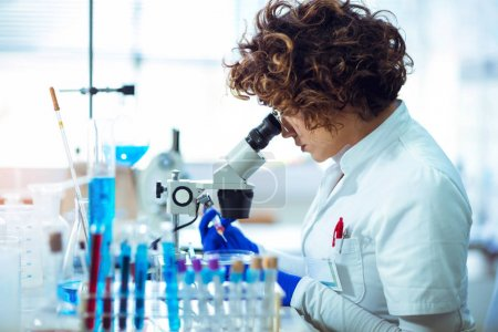 Photo for Woman scienist in laboratory. Young scientist looking through a microscope in a laboratory. Young scientist doing some research. - Royalty Free Image