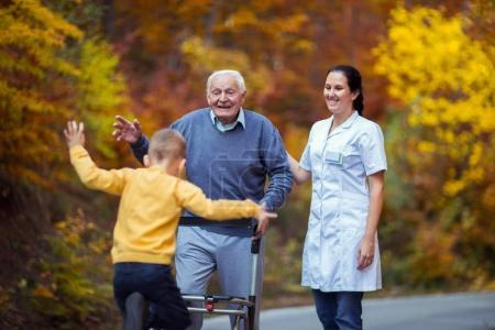 Photo pour Joyeux grand-père handicapé en marcheur accueillant son heureux petit-fils - image libre de droit