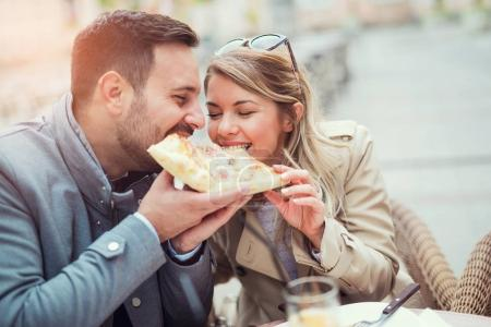 Photo for Couple eating pizza snack outdoors. - Royalty Free Image
