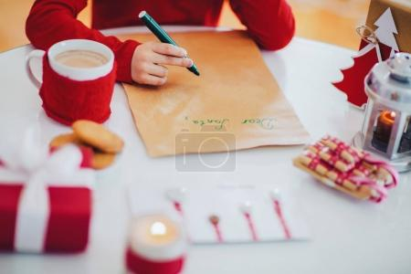 child writing letter to Santa Claus