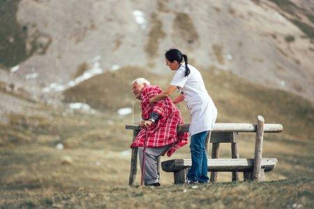 Photo pour Infirmière aidant un aîné âgé à marcher à l'air frais à l'extérieur - image libre de droit