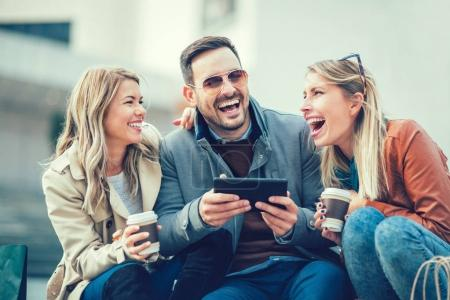 friends laughing using tablet