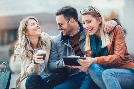 Photo pour Groupe d'amis souriants avec tablette numérique à l'extérieur - image libre de droit