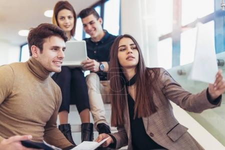 friends sitting on stairs in school