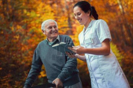 Photo pour Jeune infirmière aidant l'homme âgé dans le parc d'automne et le livre de lecture. Homme âgé utilisant un marcheur avec soignant en plein air - image libre de droit