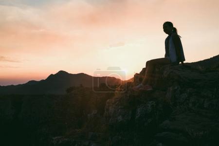 Girl sitting on mountain